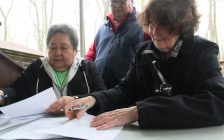 Chief Denise Stonefish, left, and former chief Greg Peters sign the land transfer agreement with the United Church of Canada on Friday. (Photo by Michael Hugall)