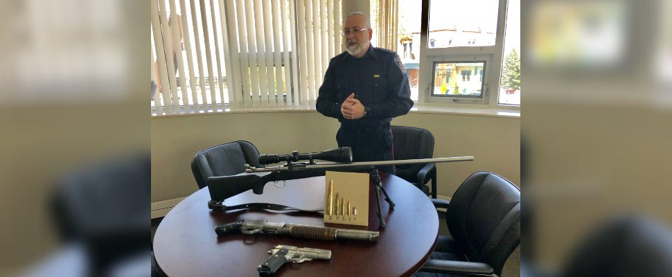 Chatham-Kent Police Constable Rob Tobin displays guns that were seized across the municipality in 2018. (Photo by Allanah Wills)