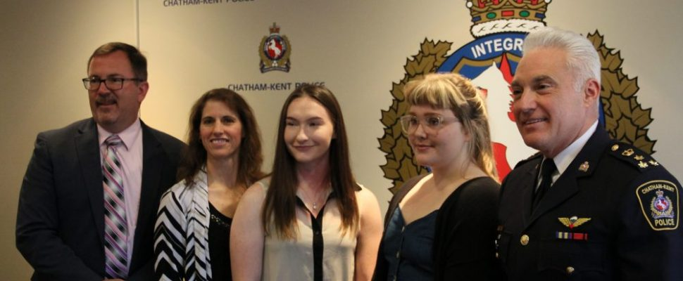 Chatham-Kent mayor Darrin Caniff, left, Const. Rene Cowell and police chief Gary Conn, right, stand for a photo with scholarship winners Kayla Coates and Abby Thompson on Tuesday.