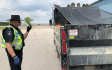 A Ministry of Finance representative conducts a fuel test on a commercial vehicle during a safety blitz in Middlesex Centre, June 19, 2019. Photo courtesy of OPP.