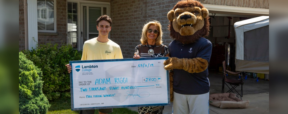 College President Judith Morris and Pounce present Adam Riggi with a cheque for free tuition. July 11, 2019. (Photo by Lambton College)