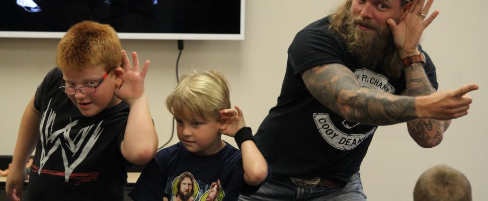 Cody Deaner, and two fans reinact poses from Hulk Hogan during a presentation on Thursday. Photo by Michael Hugall)