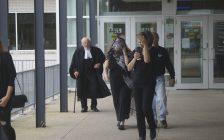 Karen Ebel-Savage leaves the Sarnia courthouse with a scarf covering her face alongside family and her defence counsel, David Stoesser. September 12, 2019. (BlackburnNews photo by Colin Gowdy)