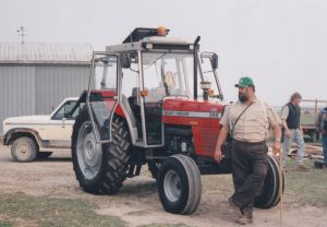 Leonard McNeil standing next to a tractor. (Photo provided by Barn McNeil)