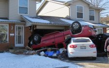 A red pickup truck crashed into 18 Jalna Boulevard, overturning onto a parked car, February 21, 2020. (Photo by Miranda Chant, Blackburn News)
