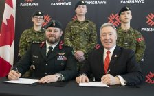 Canadian Army Reserve soldiers from 31 Canadian Brigade Group stand behind Colonel Jason Guiney of the Canadian Armed Forces and Fanshawe President Peter Devlin as they sign a Memorandum of Understanding on February 21, 2020. (Photo courtesy of Fanshawe College)