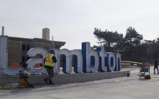 Workers installing a new sign outside Lambton College. 12 February 2020. (BlackburnNews.com photo by Colin Gowdy)