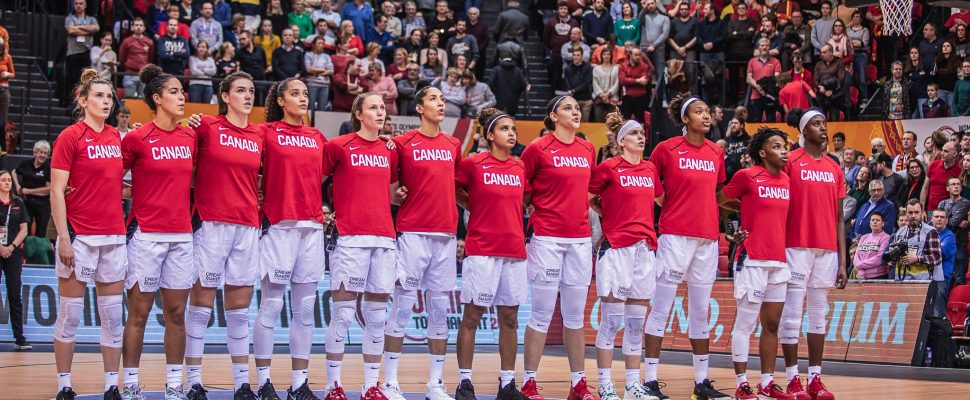 Bridget Carleton (third from left) stands with Canada's Women's Basketball ahead of a Tokyo Olympic qualifying game in Belgium. February 6, 2020. (Photo from @CanBball via Twitter)