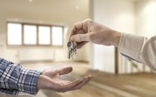 Realtor handing over keys to a house in an empty room. © Can Stock Photo / pbombaert