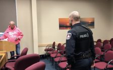 Saugeen Shores resident John Mann was escorted by police from council chambers after refusing to leave the podium. Uniformed police officer in the foreground surrounded by empty chairs approaches the podium to the back left where Mann is standing.Photo by Fiona Robertson.