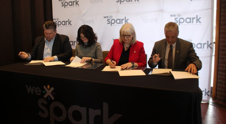 WRH CEO David Musyj, St. Clair College President Patti France, HDGH CEO Janice Kaffer and University of Windsor President Robert Gordon sign the memorandum of understanding for WE SPARK Health Institute, March 9, 2020. (Photo by Maureen Revait)