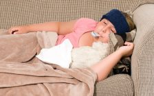 A sick child lays on a couch. File photo courtesy of © Can Stock Photo / dragon_fang