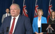 Ontario Premier Doug Ford speaks with the media at Queens Park, Toronto, as Minister of Education Stephen Lecce, left, Infrastructure Minister Laurie Scott, and Minister of Health Christine Elliott look on, June 3, 2020. Photo courtesy Premier of Ontario/YouTube.