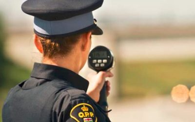 An Ontario Provincial Police officer with a radar speed gun. (Photo by OPP)