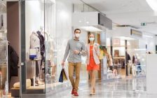 A couple wearing face masks walk through a mall. File photo courtesy of © Can Stock Photo / dolgachov