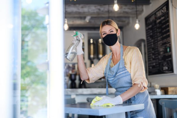 Coffee shop owner working with face mask and gloves , cleaning and disinfecting tables. © Can Stock Photo / halfpoint