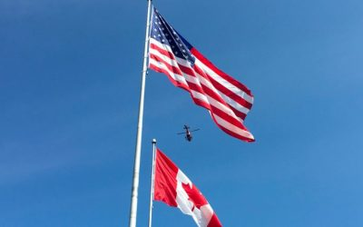 A Canadian Coast Guard helicopter flies high above the US and Canadian flags. (Photo by CCGS)