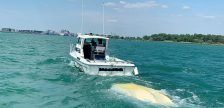 An OPP Marine Unit vessel is seen near a capsized boat on the Detroit River off LaSalle, August 8, 2020. Photo provided by Ontario Provincial Police.