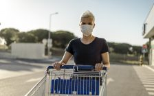 Woman wearing protective face mask with shopping cart in front of supermarket (© Can Stock Photo / malajski)