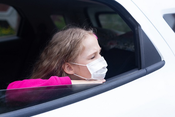A child with a face mask waits inside a vehicle. File photo courtesy of © Can Stock Photo / NataliaDuryagina