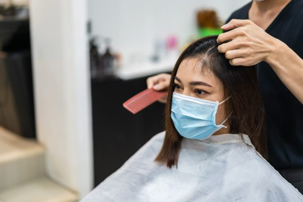 A woman wears a facemask while getting a haircut. (© Can Stock Photo / geargodz)