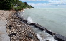 Erosion along the Lake Huron shoreline. Waves on the right lap at a break wall made up of concrete blocks. Part of eroded asphalt of a parking lot visible to the left. Lovely blue cottage in the background with lake encroaching ever closer. Photo by Bob Montgomery.