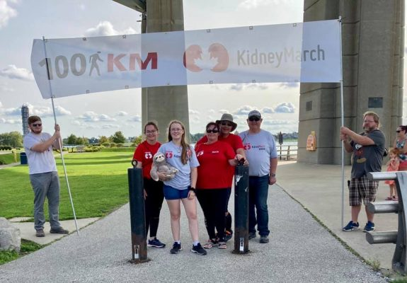 "(From left to right) Alaina, Abby, Kim and Paul Wright, and Kim's father, Wayne Freer, celebrate the family's Kidney March trek under the Blue Water Bridge. 13 September 2020. (Photo from ""Living on Love"" Facebook page)."