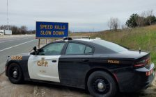 """OPP cruiser next to a """"Speed Kills - Slow Down"""" sign on the highway. (Photo by OPP West Region)"""