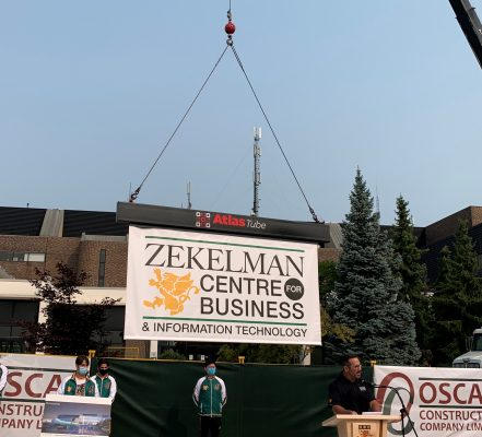 A sign identifying the future St. Clair college Zekelman Centre of Business and Information Technology is lowered into place, September 16, 2020. Photo provided by St. Clair College.