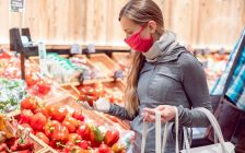 A woman wearing a face covering shops for groceries. File photo courtesy of © Can Stock Photo / Kzenon