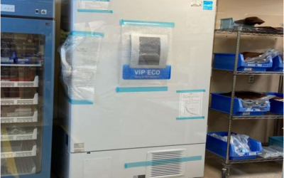 Large white freezer with digital display screen in the centre, still covered in protective shipping materials.