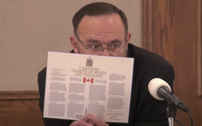 Church of God Pastor Henry Hildebrandt holds up a copy of the Canadian Charter of Rights and Freedoms during an indoor-service, January 31, 2021. Screen capture from Hildebrandt YouTube channel.