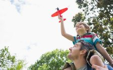 A little boy sits on his father's shoulders flying a toy plane. File photo courtesy of © Can Stock Photo / 4774344sean