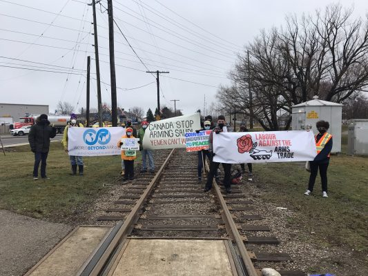 A group of activists gathers on the CN railway near General Dynamics to protest arms exports to Saudi Arabia. March 26, 2021. (Photo supplied by Labour Against The Arms Trade Canada)
