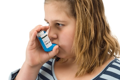 A girl using her asthma inhaler. File photo courtesy of © Can Stock Photo / dragon_fang.