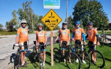 """(From left to right) Jeff Burchill, Kathy Johnson, Ken MacAlpine, Paul Eastman and Pete Cobb of the Bluewater International Granfondo next to new """"Share the Road"""" street signs. October 2021. (Photo submitted by B.I.G.)"""
